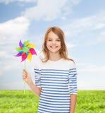 有五颜六色的风车玩具的微笑的孩子 免版税库存图片