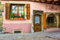有五颜六色的鲜花的壮观的减速火箭的房子在角落 免版税库存照片