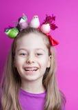 有五颜六色的鸟的愉快的微笑的儿童女孩在头 免版税库存图片