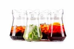 有五颜六色的鸡尾酒的四个玻璃水瓶投手 免版税库存图片