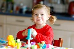 有五颜六色的黏土的可爱的逗人喜爱的矮小的小孩女孩 健康小儿童游戏和创造从戏剧面团的玩具 免版税库存照片