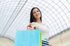 有五颜六色的购物袋的一个愉快的少妇从花梢商店 库存图片
