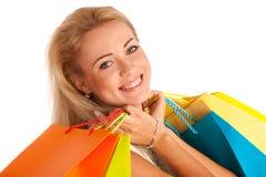 有五颜六色的购物袋的可爱的白肤金发的女孩 免版税库存图片