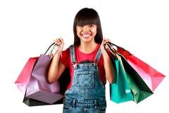 有五颜六色的购物袋的小亚裔女孩 免版税库存照片