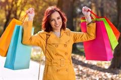 有五颜六色的购物袋的微笑的妇女 免版税库存图片