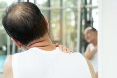 有亚裔的老人在他的肩膀和脖子的痛苦 图库摄影