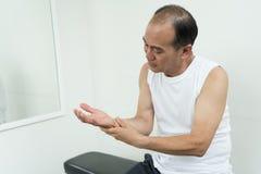 有亚裔的老人腕子痛苦或伤害 图库摄影