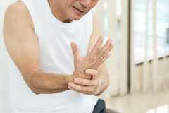 有亚裔的老人腕子痛苦或伤害 库存图片