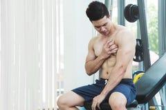 有亚裔肌肉的人在他的胸口的痛苦 免版税库存图片