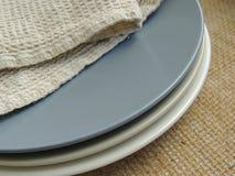 有亚麻制毛巾的表面无光泽的板材在粗麻布背景,食物照片支柱 免版税库存图片