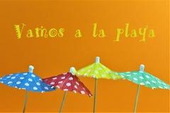 有些伞, vamos的概念图象有文本的la playa =让去海滩翻译 免版税库存图片