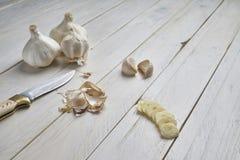 有些头、有些丁香和切片静物画在一张白色木桌上的大蒜 免版税图库摄影