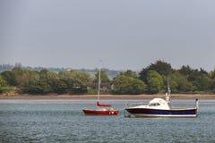 有些小船在与树的爱尔兰海湾停泊了在背景中 免版税库存照片