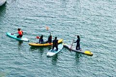 有些男孩和女孩在海的表面上的一个委员会用浆划 免版税库存照片
