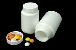 有些药片与两白色瓶子的不同的颜色 免版税库存照片