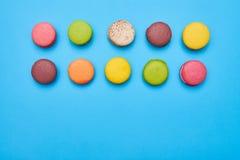 有些蛋白杏仁饼干在两条线安排了被隔绝在蓝色flatlay 免版税库存图片