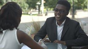 有交谈和做文书工作的美国黑人的同事在咖啡馆 股票视频