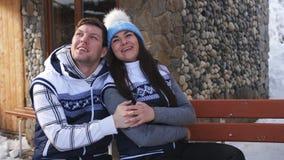 有交谈和挥动在长凳的男人和妇女开会在冬天瑞士山中的牧人小屋附近在山 股票视频
