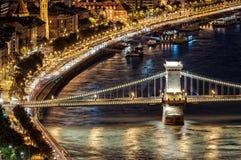 有交通的多瑙河在河岸和有启发性铁锁式桥梁在布达佩斯在晚上 匈牙利,欧洲 免版税图库摄影