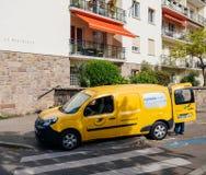 有交付小包的工作者的黄色van la Poste搬运车 库存照片