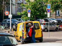 有交付小包的工作者的黄色van la Poste搬运车 库存图片