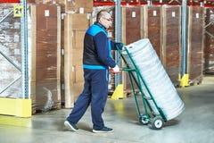 有交付推车的工作者在仓库里 免版税图库摄影
