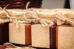 有产品的玻璃瓶子手工制造与纸盒盖栓与与空的标签的麻线文本的在商店的柜台 免版税库存图片