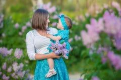 有享受在一个令人敬畏的地方的女儿的愉快的母亲妈妈时间在淡紫色注射器灌木之间 有篮子的小姐有很多花 免版税库存照片