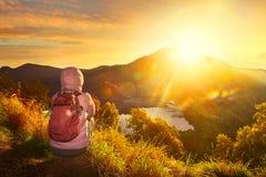 有享受日出视图的背包徒步旅行者的妇女在高山 免版税图库摄影