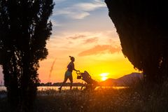 有享受母性的婴儿推车的连续母亲在日落登陆 免版税图库摄影