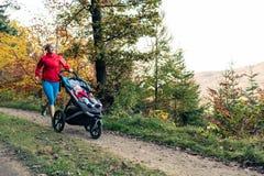有享受母性的婴儿推车的连续母亲在秋天sunse 图库摄影