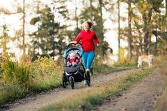 有享受母性的婴儿推车的连续母亲在秋天sunse 免版税图库摄影
