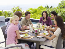 有享受膳食的朋友的妇女在露台 免版税库存图片