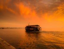 有享用咖啡浮游物的人的小船对海岸 免版税库存照片