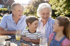 有享用室外夏天快餐的孙的祖父母在咖啡馆 免版税图库摄影