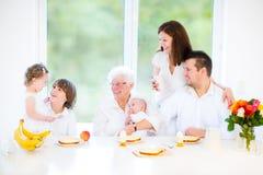 有享用早餐的三个孩子的愉快的家庭 免版税库存照片