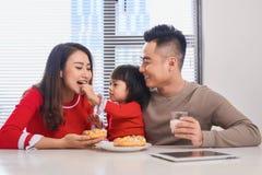 有享用早餐的孩子的愉快的年轻家庭在有一个大庭院视图窗口的一个白色晴朗的餐厅 免版税库存照片