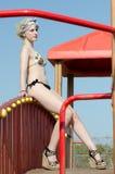 有亭亭玉立和运动获得身体佩带的比基尼泳装的白肤金发的夫人在乐趣公园旁边的乐趣 免版税库存图片