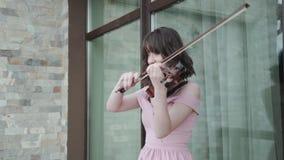 有亭亭玉立的腿的快乐的妇女在阳台和戏剧走在中提琴 股票录像