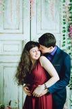 有亲吻在屋子里的女孩的可爱的人 免版税图库摄影
