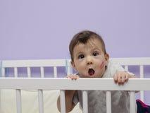 有亲吻标记的乐趣婴孩在摇篮。 库存照片
