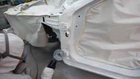 有人工呼吸机的妇女在面孔处理使用有白色染料的车身气刷在车库在修理以后 股票视频