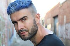 有人工地色的蓝色被洗染的头发咬边的发型、胡子和穿甲的英俊的时髦的年轻人与拷贝空间 免版税库存照片