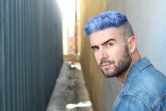 有人工地色的蓝色被洗染的头发咬边的发型、胡子和穿甲的英俊的时髦的年轻人与拷贝空间 库存照片