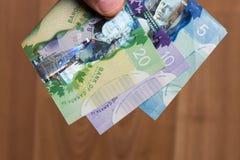有人手指的加拿大Dolar 库存图片