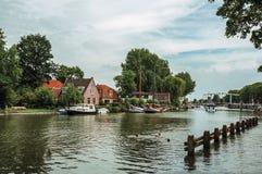 有人游泳的Vecht在砖houses's码头停住的河,小船和多云蓝天在韦斯普 图库摄影