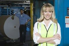 有人的微笑的妇女由巨大的纸卷在工厂 免版税库存照片