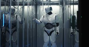 有人的特点的机器人在数据中心的检查服务器 图库摄影