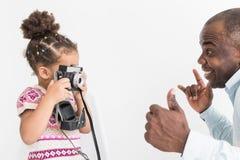 有他为照相的逗人喜爱的矮小的女儿的年轻父亲在一台老葡萄酒照相机 免版税库存图片
