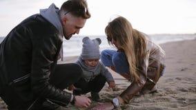 有他们的使用与在冷的多云刮风的天气、男人和妇女的沙子的儿童小孩男孩的年轻父母帮助小 股票视频